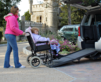 woman assisting senior woman getting inside the car