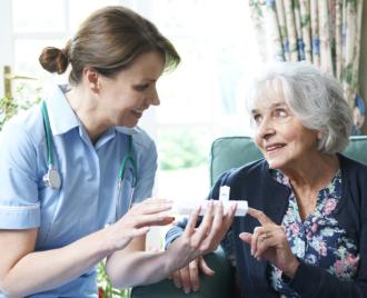 caregiver giving medicine to elderly woman